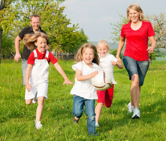 Family enjoying time playing in a grassy field
