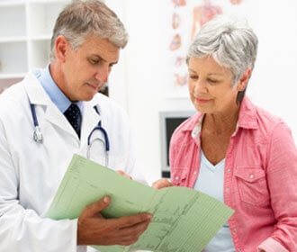 A Woman Looking Over Documents With Her Doctor