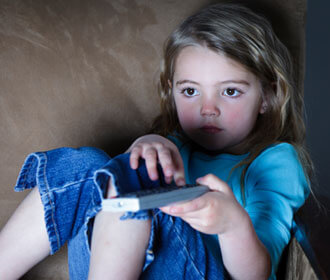 Child Sitting On The Couch Holding Remote and Watching TV
