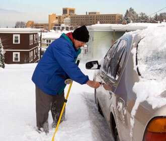 Man shoveling snow from around car